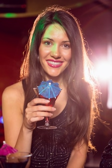 Pretty brunette drinking a cocktail