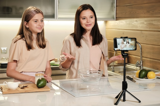 カジュラウェアを着たかなりブルネットの女性と彼女の10代の娘が、オンライン視聴者のためにキッチンでライブストリームの料理動画を制作しています