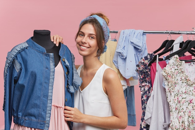 Pretty brunette female wearing white t-shirt and scarf on head, standing near mannequin with denim jacket and pink dress, standing in fitting room, having good mood. selecting clothes for party