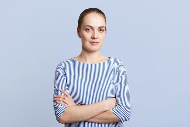 Симпатичная брюнетка женщина носит полосатую элегантную блузку, держит руки сложенными, имеет серьезное выражение лица, внимательно слушает собеседника, изолированного над синей стеной. люди, концепция выражения лица