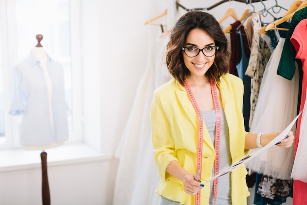 A pretty brunette girl in a grey dress and yellow jacket is standing near clothes in workshop studio. she holds a large sketch  in a hand and smiles to the camera.