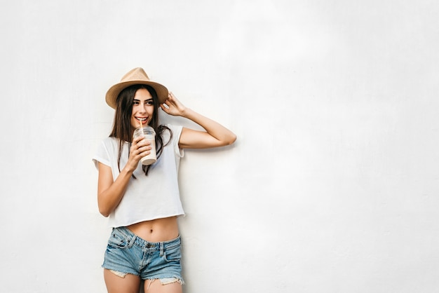 Pretty brunette girl in hat with coffee and white wall behind, copy space.