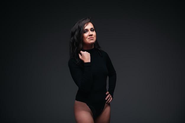 검은 벽에 bodysuit에서 예쁜 갈색 머리 소녀