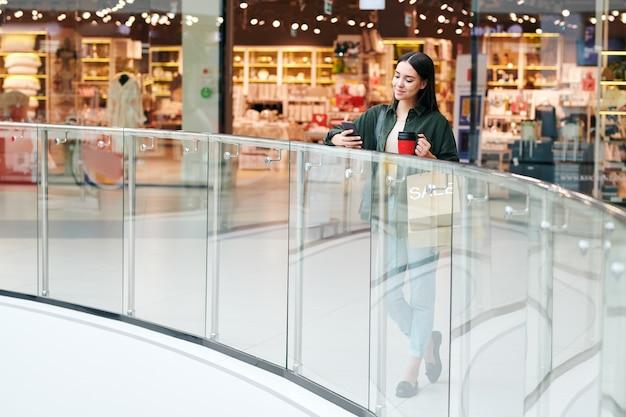 대형 무역 센터 내부의 난간에 의해 서 세련된 캐주얼에 예쁜 갈색 머리 소녀, 커피를 마시고 스마트 폰에서 스크롤