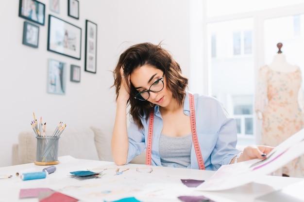 Una bella ragazza mora è seduta al tavolo nello studio del laboratorio. la ragazza in camicia blu è impegnata a guardare gli schizzi nell'album.