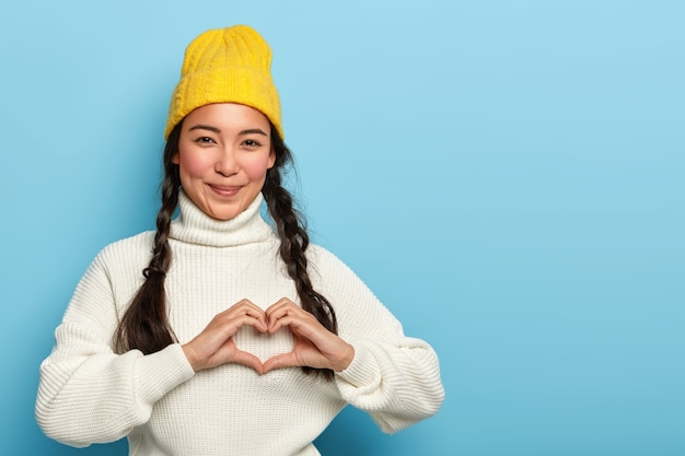 Pretty brunette girl makes heart hand sign, smiles pleasantly, wears yellow hat and white sweater, expresses love and affection, has satisfied expression, models against blue background, copy space
