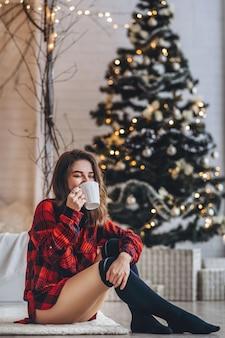 赤いシャツと暖かい靴下で床に座っているかなりブルネットの女の子とコーヒーとクリスマスツリーの後ろ