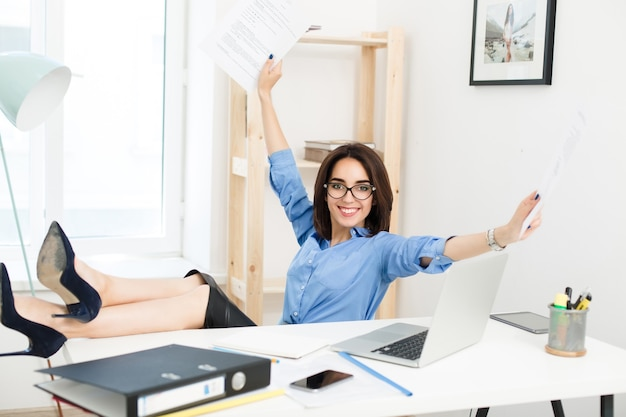 A pretty brunette girl, sitting at the tably in office, crosed legs on the table. she wears blue shirt and black skirt with shoes. she looks very energetic.