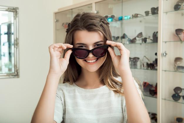 Ragazza graziosa del brunette che sorride, provando sugli occhiali da sole in negozio di ottica