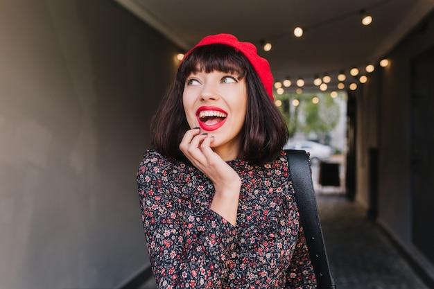 Bella ragazza mora che indossa abiti in stile francese, toccando il suo viso, ha ricordato qualcosa di divertente. ritratto di adorabile giovane donna con capelli scuri corti in berretto rosso e abito vintage divertendosi al chiuso
