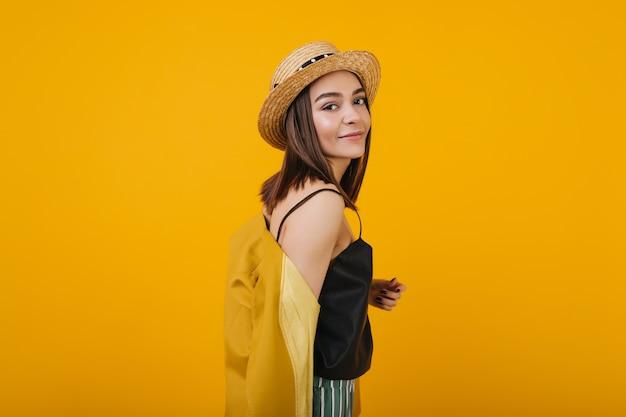 かなりブルネットの女の子は麦わら帽子をかぶっています。孤立した壮大な女性の屋内肖像画。