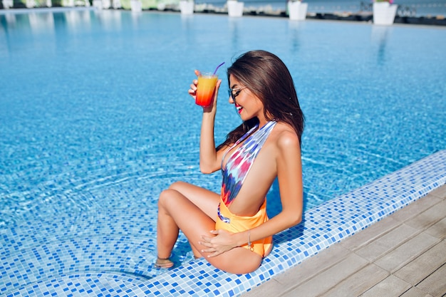 Pretty brunette girl with long hair is sitting on the boder of pool. she wears colorful swimsuit and sunglasses. she holds cocktail and looks happy.