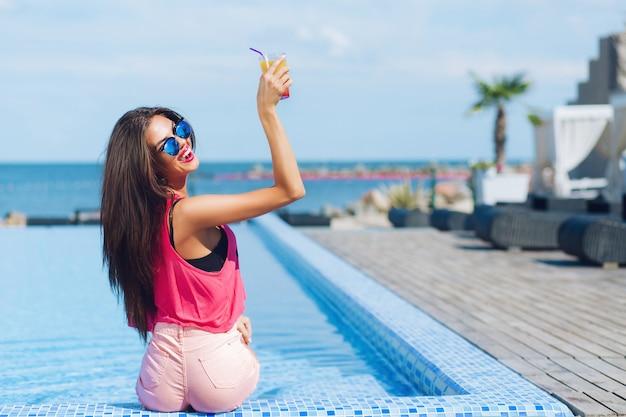 Bella ragazza bruna con i capelli lunghi è seduta vicino alla piscina. tiene il suo drink sopra e sorride alla telecamera. vista dal retro.