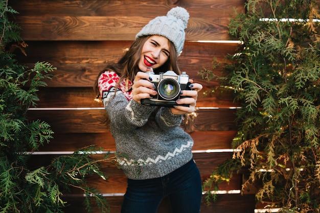 Ragazza graziosa del brunette con capelli lunghi in vestiti di inverno che hanno divertimento con la macchina fotografica sui rami verdi circondano in legno.