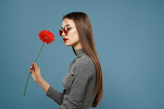 赤い花のかなりブルネットは暗いメガネの青い背景のファッショナブルな髪型を回復します