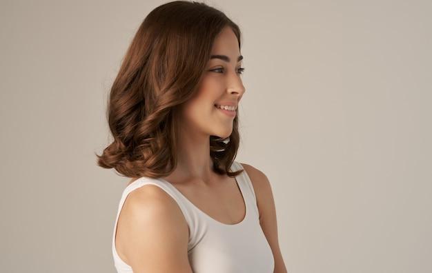 白いtシャツの笑顔の感情ベージュの背景でかなりブルネット