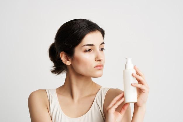 흰색 탱크 탑 크림 피부 보습 화장품에 예쁜 갈색 머리. 고품질 사진
