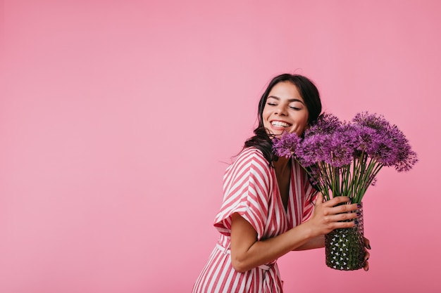 예쁜 갈색 머리는 선물 꽃을 즐기면서 눈부시게 웃고 있습니다. 행복에서 그녀의 눈을 감고 핑크 스트라이프 톱에 여자의 초상화.