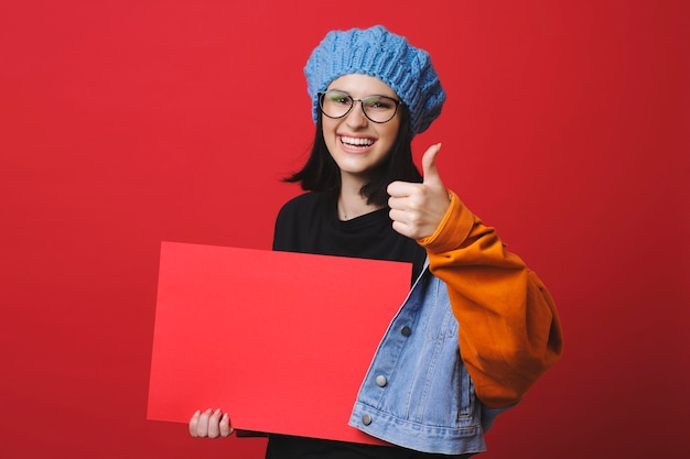Pretty brunette in jacket holding thumb up while showing blank red paper smiling at camera