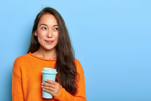 Pretty brunette japanese woman has long hair, wears vivid orange warm sweater, holds coffee to go