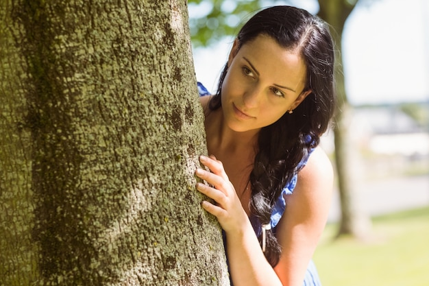 Pretty brunette leaning against a tree