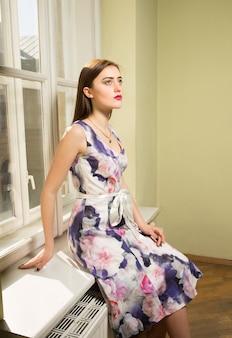 晴れた日に窓にポーズをとって、長いドレスを着てかなりブルネットのモデル