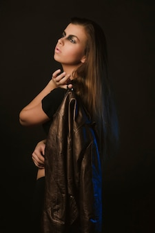스튜디오에서 가죽 재킷을 들고 예술 화장을 한 예쁜 갈색 머리 모델