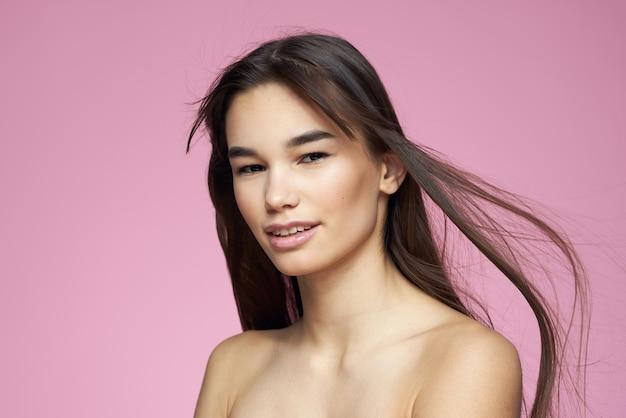 Симпатичная брюнетка с обнаженными плечами, прозрачная кожа, розовая