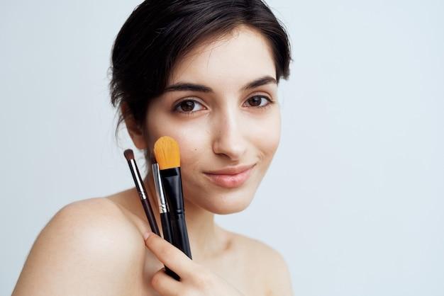 かなりブルネットの裸の肩のシャワーメイクブラシ化粧品のクローズアップ。高品質の写真