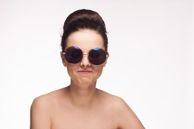 かなりブルネットの裸の肩のサングラスは肌の明るい背景をクリアします