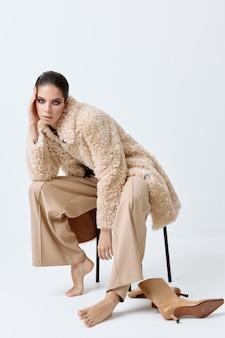 裸足のスタイリッシュな服の椅子に座ってかなりブルネットのポーズ