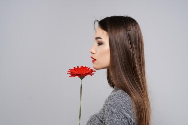 かなりブルネットの赤い花明るいメイクスタジオ灰色の背景。高品質の写真