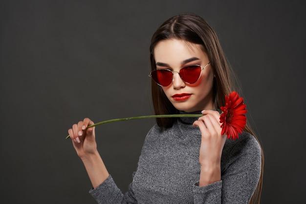 かなりブルネットの赤い花のエレガントなスタイルのロマンス。高品質の写真
