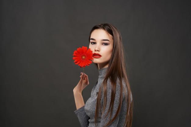 顔のメイクの暗い背景の近くのかなりブルネットの赤い花