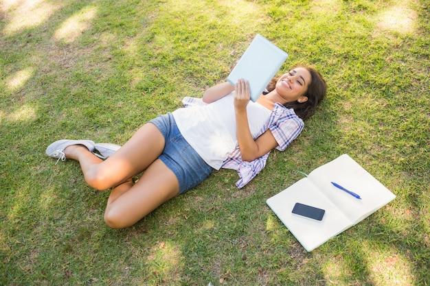 잔디에서 편안 하 고 책을 읽고 예쁜 갈색 머리