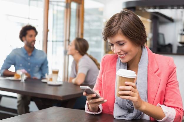 Pretty brunette sending a text drinking coffee