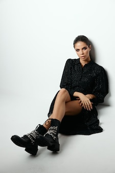 かなりブルネットは床に座る黒いドレスのファッションブーツ