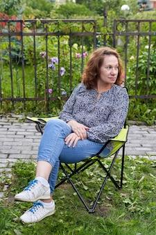 かなりブルネットは庭のピクニックチェアに座っています。屋外の椅子でリラックスした女性の肖像画