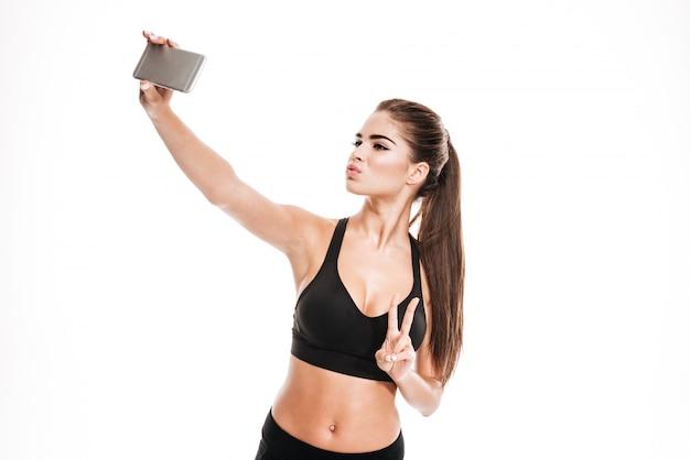 예쁜 갈색 머리 스포츠 여자 그녀의 휴대 전화로 selfie를 복용
