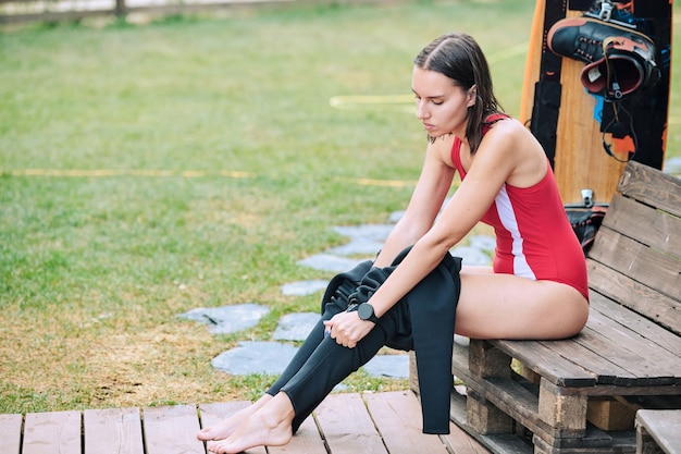 Pretty brunette sportswoman with dark wet hair putting on black leggins while sitting on wooden bench before surfboard training