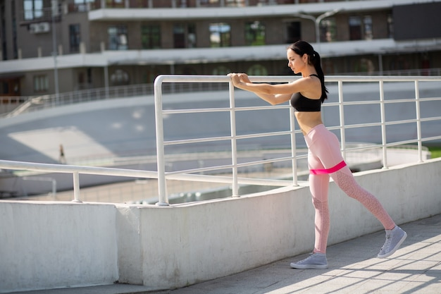 Pretty brunette sporty woman doing stretching excercises with an elastic resistance band at the stadium. space for text