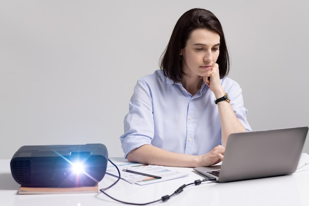 Pretty brunette student looking at laptop display while sitting by desk with switched on projector and preparing presentation before seminar