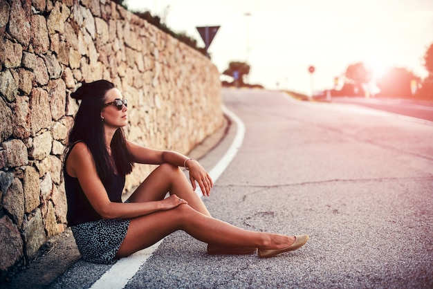 Pretty brunette tourist girl sitting on the road