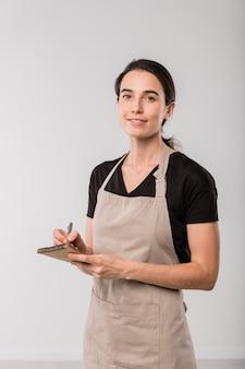 Симпатичная брюнетка официантка кафе в фартуке делает заметки в небольшом блокноте, стоя перед камерой в изоляции