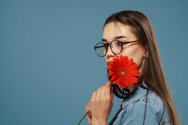Симпатичная брюнетка в очках с красным цветком возле лица гламур синем фоне