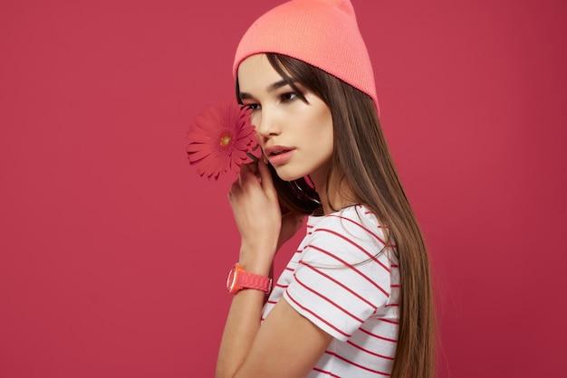 孤立した背景をポーズピンクの帽子の花を身に着けているかなりブルネット
