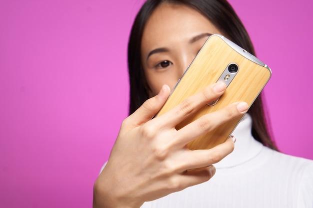 オンラインでインターネットをチャットしている彼女の手に電話を持つかなりブルネット