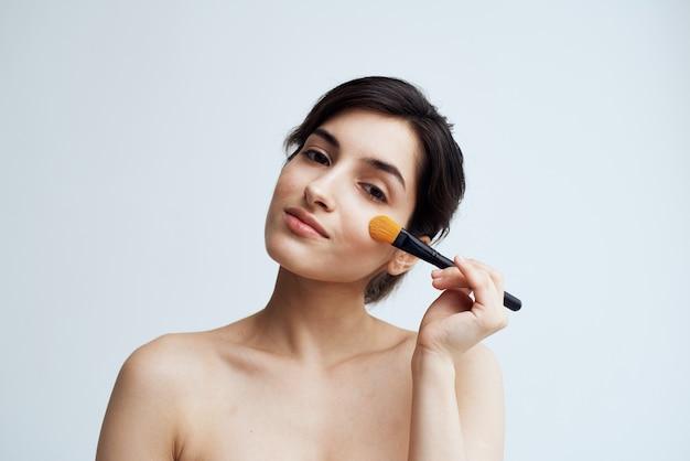 魅力的な外観のために彼女の顔に化粧をしている裸の肩を持つかなりブルネット。