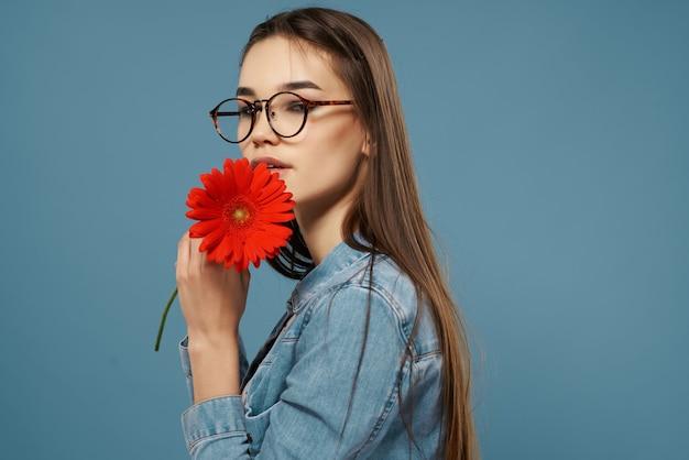 Симпатичная брюнетка в очках с красным цветком джинсовая куртка элегантность романтика