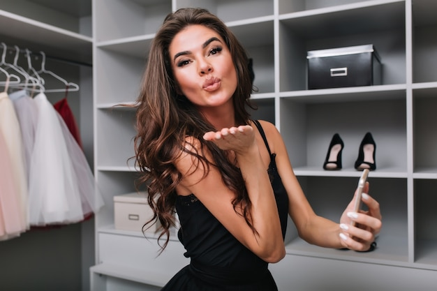 Pretty brunette with long brown curly hair, young girl sending kiss, holding smartphone in hand. big nice dressing room. she sending kiss. wearing stylish dress.